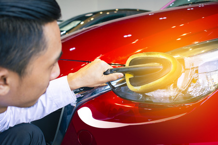 Asian man is wipping car with LED headlight for customers.Using wallpaper or background for transportation and automotive image.