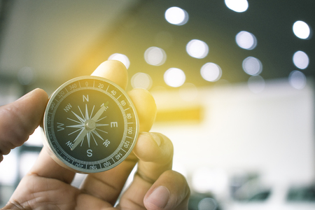holding compass on blurry background. Using wallpaper or 