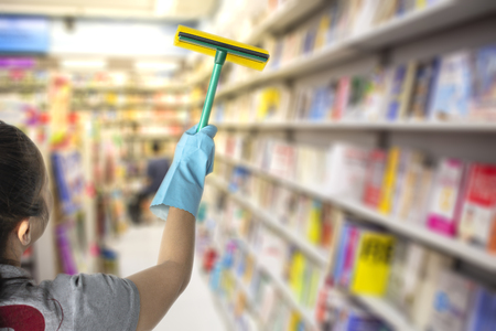 Female cleaning staff in library, book room or bathroom blurry background Metaphor for cleaning Get rid of germs In bathroom, home office.For reliability And satisfaction of service and customers.