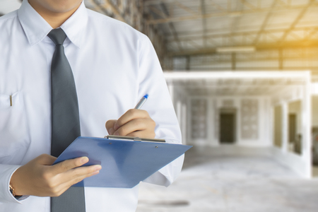 Scrittura di ispezione dell'ingegnere maschio in fabbrica Con nota sul blocco note o sfondo sfocato del settore.Ispezione di qualità della metafora o velocità di produzione Per la migliore qualità per i clienti.
