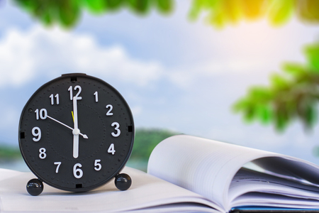 Holding clock on sea blurred background The time 6:00 am or pm and noon or midnight for made clock isolated or White background Copy space move to clipping path