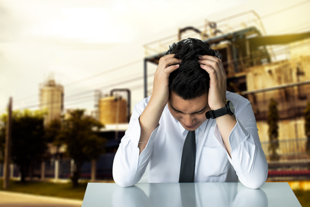 Asian businessman sad sitting or strait business man sitting chair Express feeling on factory background Metaphor for Success finance Dealing buying or Insurance image