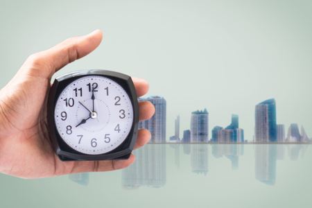 Holding clock on city blurred background The time 8:00 am or pm and noon or midnight for made clock isolated or White background Copy space move to clipping path