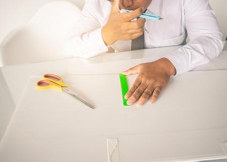 Asiatischer Mann Scherenschnitt mit Schere für Bastelpapier und erstellen Sie eine Box. Im weißen Hintergrund des Büros
