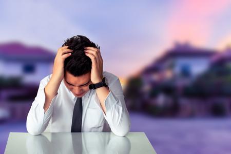 Homme d'affaires asiatique triste assis ou homme d'affaires détroit assis sur une chaise Exprimer le sentiment sur fond flou à la maison Métaphore de la réussite financière Traiter l'achat ou l'image d'assurance Banque d'images