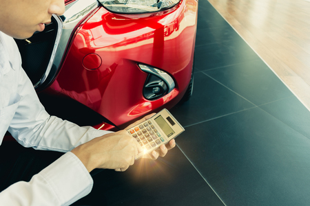 This career salesman calculating on calculator car price in showroom