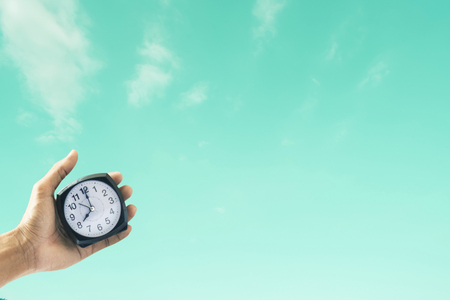 Holding clock on sky blurred background. Metaphor success freedom imagination concept image Stockfoto