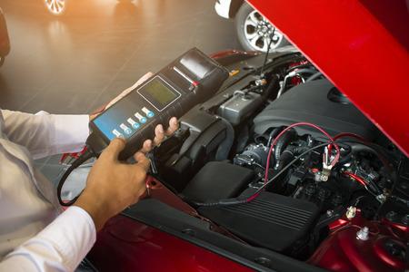 Inspectie van de mens met batterijcapaciteitstester Voltmeter.voor serviceonderhoud van industriële tot motorreparatie.In fabriekstransport auto automobiel afbeelding