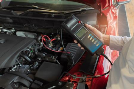 Inspection de l'homme tenant le voltmètre du testeur de capacité de la batterie.pour la maintenance du service de réparation industrielle à moteur.Dans l'image automobile automobile de transport d'usine