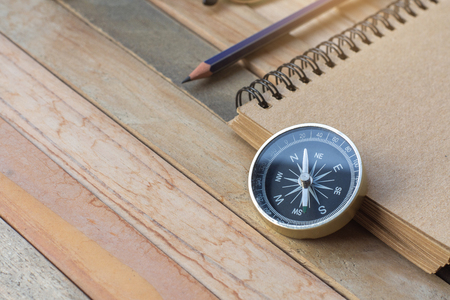 Compass, Notepad with pencil on wood board background.using wallpaper for education, business photo.Take note of the product for book with paper and concept, object or copy space.