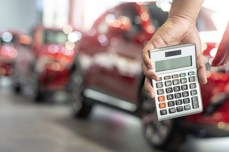 man holding calculator for business finance on car showroom blurred bokeh background.for automotive automobile or transportation transport