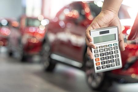 man holding calculator for business finance on car showroom blurred bokeh background.for automotive automobile or transportation transport