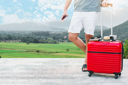 Man holding Red luggage with passport on blurred city background  for activity lifestyle outdoors freedom or travel tourism  andinspiration backpacker alone tourist image