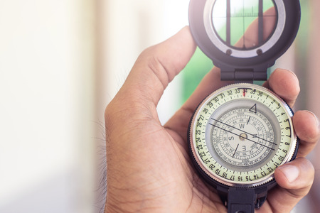 holding compass on blurred background. Using wallpaper or background travel or navigator image.
