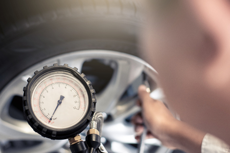 Asian man car inspection Measure quantity Inflated Rubber tires car.Close up hand holding machine Inflated pressure gauge for car tyre pressure measurement for automotive, automobile image Stock Photo