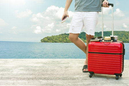 Man holding Red luggage with passport on blurred city background for activity lifestyle outdoors freedom or travel tourism andinspiration backpacker alone tourist image Stock Photo