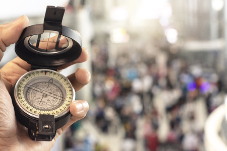 man holding compass on blurred background. for activity lifestyle  outdoors freedom or travel tourism and inspiration backpacker alone  tourist travel or navigator image. Stock Photo