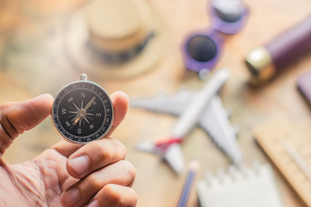 Man holding compass on blurred note with passport, binoculars, pencil, airplane, paper map background for travel adventure discovery image