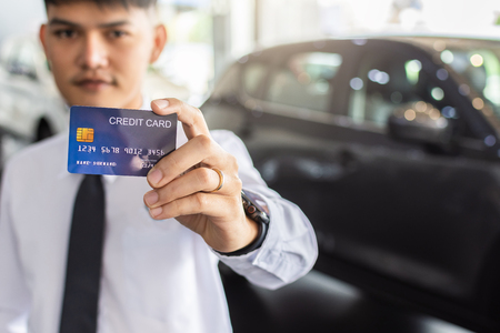 Asian man holding credit card for car blurred bokeh background e-shopping marketing digital, consumer purchase shopping internet online image
