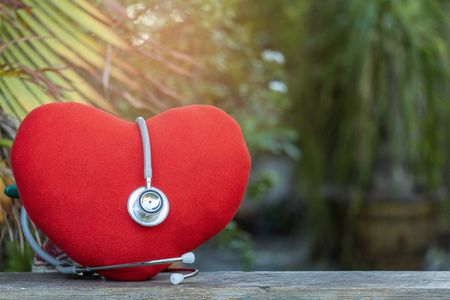 Heart with medical stethoscope on wood backdrop on tree blurred background.for health care emergency take care of warning of danger health. Stock Photo