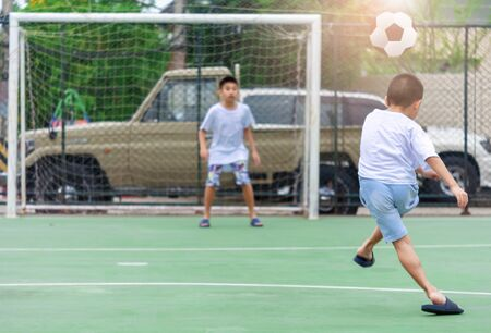 Children are wearing slippers playing football With blurred background to show movement.To exercise After school.