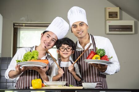 Asian woman young mother and father with son boy cooking salad food with vegetable holding tomatoes and carrots, bell peppers on plate for happy family cook food enjoyment lifestyle kitchen in home