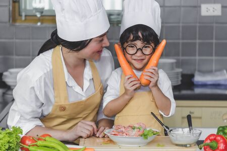 Asian woman young mother with son boy cooking salad food  with vegetable holding two carrots and tomatoes, bell peppers for happy family cook food enjoyment lifestyle kitchen Stock Photo
