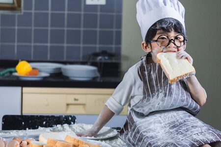 Asian Boy wear glasses cooking with white flour Kneading bread dough teaches children practice baking ingredients bread, egg on tableware in kitchen lifestyle happy Learning life with family Fun to learn Stock Photo