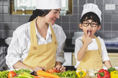 Asian woman young mother with son boy cooking salad food  with vegetable holding two tomatoes and carrots, bell peppers for happy family cook food enjoyment lifestyle kitchen