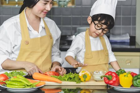Asian woman young mother with son boy cooking salad mom sliced vegetables food son tasting salad dressing with vegetable carrots and tomatoes, bell peppers for happy family cook food enjoyment lifestyle kitchen