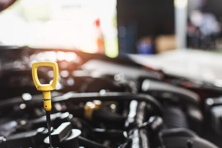 Man service mechanic maintenance inspection service maintenance car Check engine oil level car in garage showroom dealership blurred background.