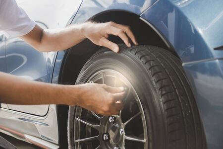 Asian man car inspection Measure quantity Inflated Rubber tires car.Close up hand holding machine Inflated pressure gauge for car tyre pressure measurement for automotive, automobile image Фото со стока