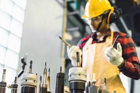 Ispezione di fabbrica di ingegnere uomo asiatico con ingegnere di affari uomo tenere strumento nell'industria che lavora il controllo della lavorazione dei metalli nell'industria In una fabbrica di plastica per auto
