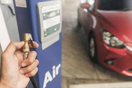 Asian man car inspection Measure quantity Inflated Rubber tires car.Close up hand holding machine Inflated pressure gauge for car tyre pressure measurement for automotive, automobile image Reklamní fotografie - 134462849