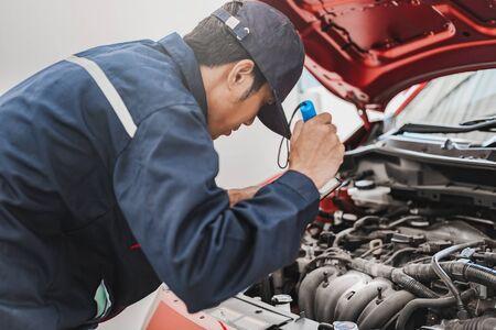 Inspección mecánica del hombre asiático Brille un error de comprobación del motor de un coche de la antorcha en el motor. Coche azul para el seguro de mantenimiento del servicio con el motor del coche.