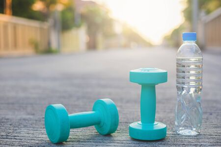 dumbbell weights and bottle on street blurred background.Metaphor Fitness and workout concept exercise Health lifestyle muscle with  take care of your health copy for advertising