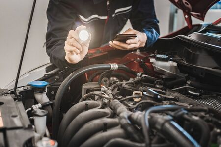 Asian Man mechanic inspection Shine a torch on car engine checking bug in engine from application smartphone. Red car for service maintenance insurance with car engine.