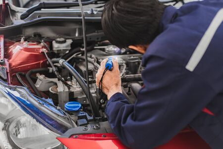 Asian Man mechanic inspection Shine a torch car engine checking bug in engine from application smartphone.Red car for service maintenance insurance with car engine.for transport automobile automotive Foto de archivo