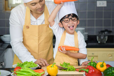 Asian man young Father Wear chef hat with son boy cooking salad food with vegetable holding two carrots and tomatoes, bell peppers for happy family cook food enjoyment lifestyle kitchen