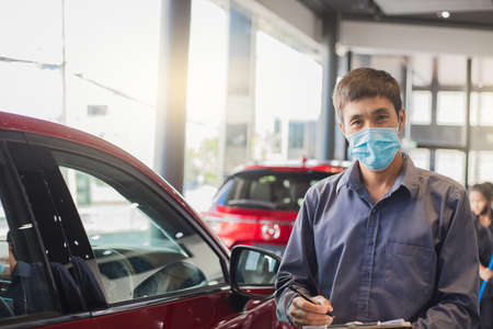 Asian saleman wear surgical mask working in inspector checking writing on clipboard in garage of dealership Wait mechanic In showroom car and insurance new normol covid-19 in showroom dealership Reklamní fotografie
