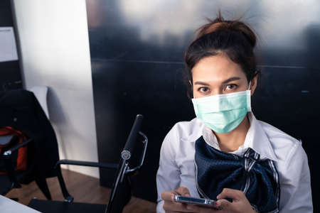 Asian woman saleman wear surgical mask working in inspector checking news covid19 from smartphone in garage of dealership Wait mechanic In showroom car and insurance new normol covid-19 in dealership Stock fotó