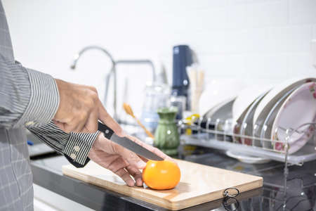 Blurred man asian cooking in kitchen of home He hands cutting vegetables and cutting fruit in the kitchen   to great hand on microwave in kitchen blurred background