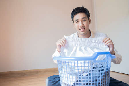 Asian man husband working homework.He is preparing clothes in basket to wash to washing machine for service lifestyle family togetherness in home