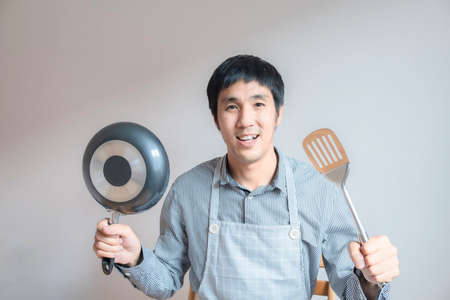 man asian cooking in kitchen of home He holds bowl and  spatula  to great hand on microwave in kitchen service lifestyle family togetherness in home