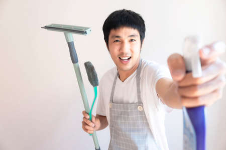 Asian male inspector smile to cleaning staff in bathroom disinfectant sprayers and germs  Metaphor for cleaning Get rid of germs In bathroom, home office.For reliability And satisfaction of service Stock fotó
