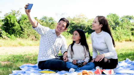 Family trip father mother and  daughter enjoy picnic freedom in garden nature.lifestyle family vacation caucasian asian.one day trip new normol during Coronavirus disease covid-19 so selfie smartphone