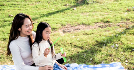 Asian portrait family trip father mother and daughter enjoy relaxation Blowing bubbles with family to lifestyle freedom family vacation caucasian asian.one day trip new normol togetherness