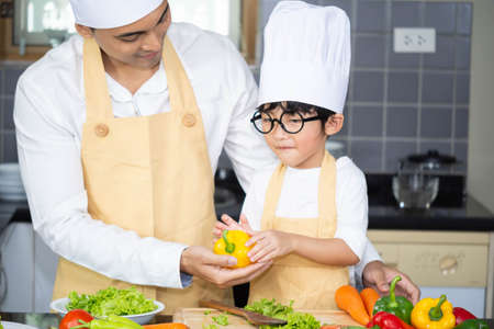 Asians Father Wear chef hat for son boy holdind wooden spoon cooking salad food with vegetable holding tomatoes and carrots, bell peppers on plate for happy family cook food enjoyment lifestyle kitchen in home