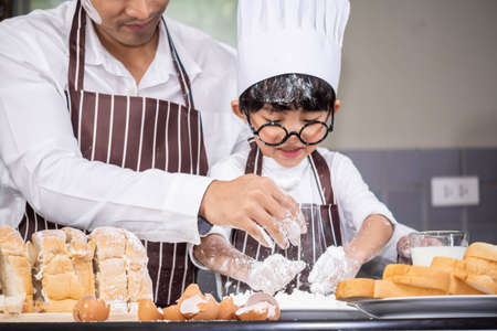 Asian Boy wear glasses Tease dad cooking with white flour Kneading bread dough teaches children practice baking ingredients bread, egg on tableware in kitchen lifestyle happy Learning life with family Fun to learn