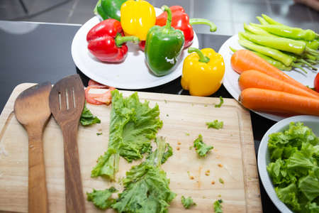 wooden spoon cooking salad food with vegetable holding tomatoes and carrots, bell peppers on plate for happy family cook food enjoyment lifestyle kitchen in home